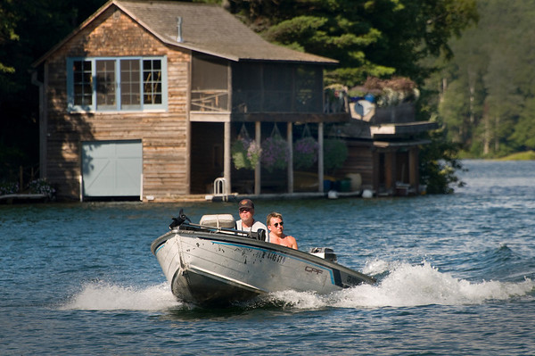 A fishing boat cruises by a boat house on Lake Owen near Cable, Wisconsin. (c) 2011 Tom Kelly